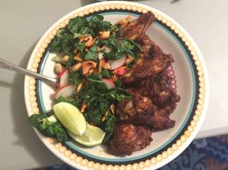 Moroccan chicken wings with bok choy, carrots, cashew, and radish slaw with a sesame dressing